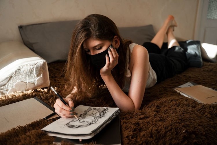 Woman wearing mask drawing in book on bed