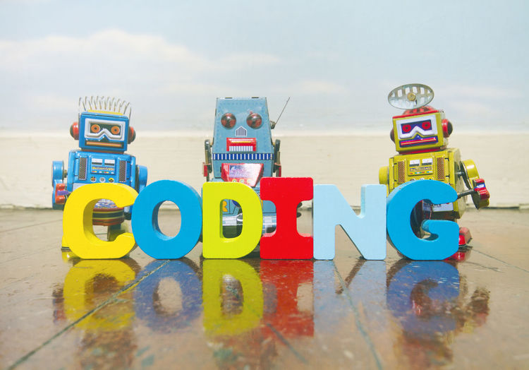CODING in wooden letters with robot toys Computer Coding Learning Robots Word Blue Sky And Clouds Childhood Cloud - Sky Educational Learning Code Multi Colored Play Preschooler Toy Toy Robots Wooden Floor Wooden Leter Wooden Letters Word Coding