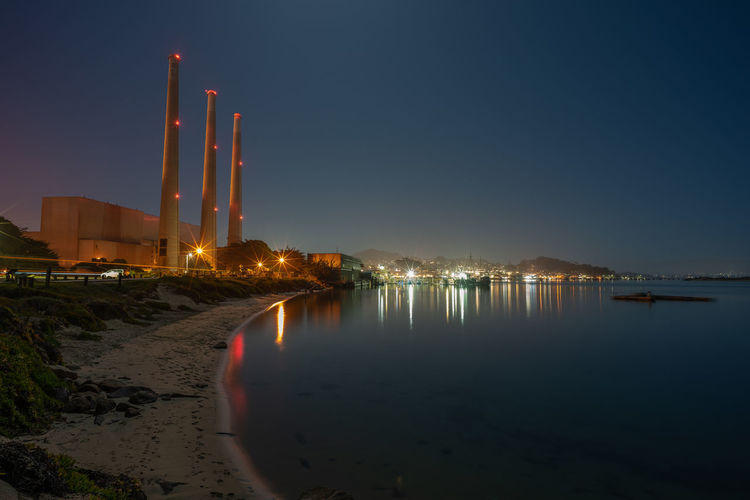 Illuminated factory by sea against clear sky at night