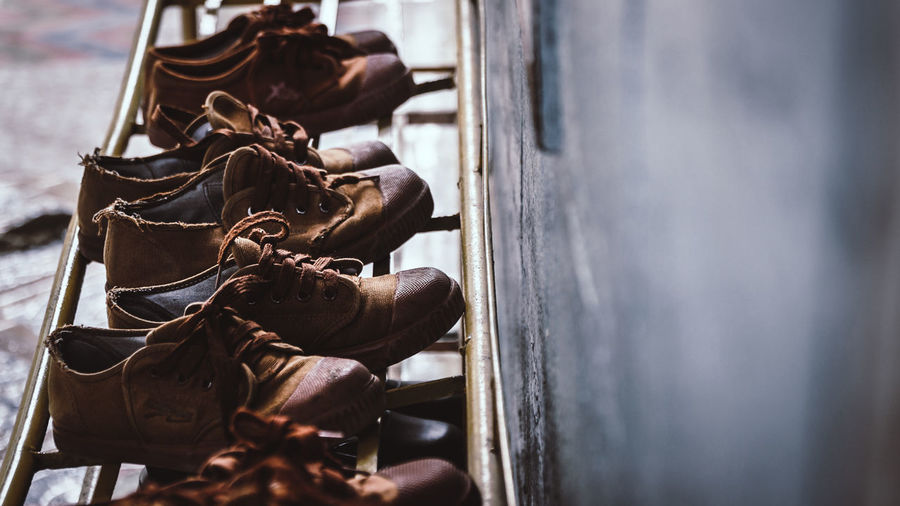 High angle view of brown shoes on rack by wall