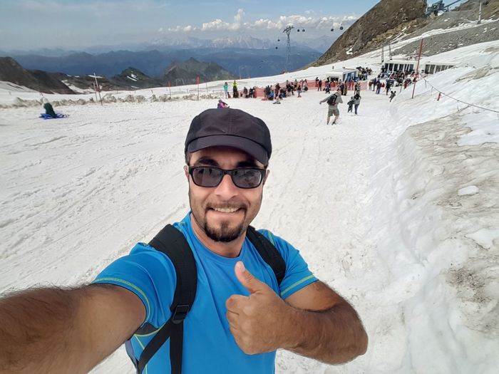 Smiling man taking selfie while standing on snowy field
