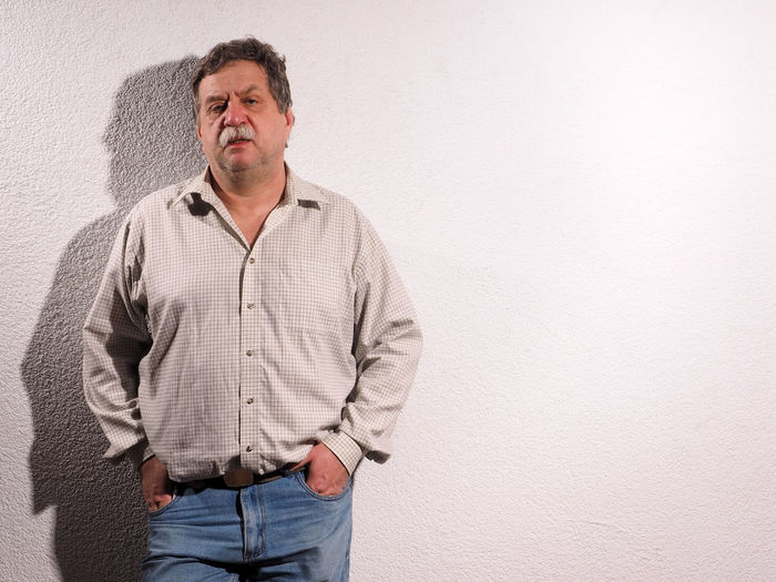 Portrait of man with hands in pocket standing against wall