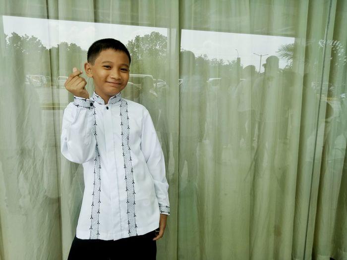 Portrait of confident boy standing against window