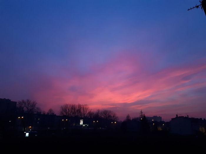 Silhouette city against sky at dusk
