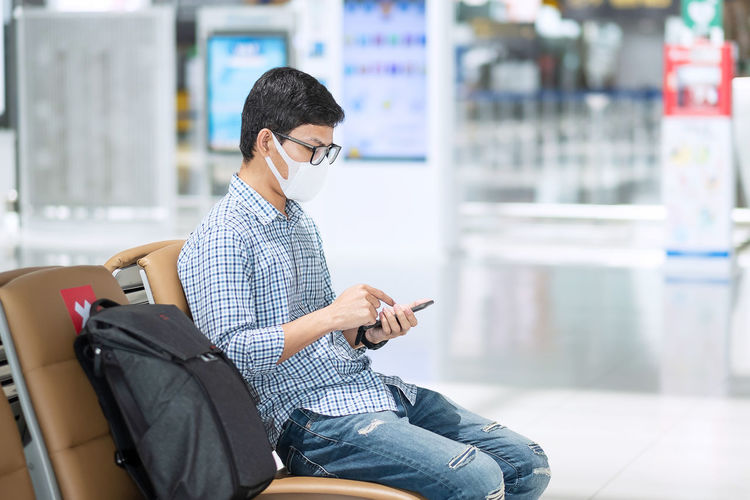 Man with mask using mobile phone in airport