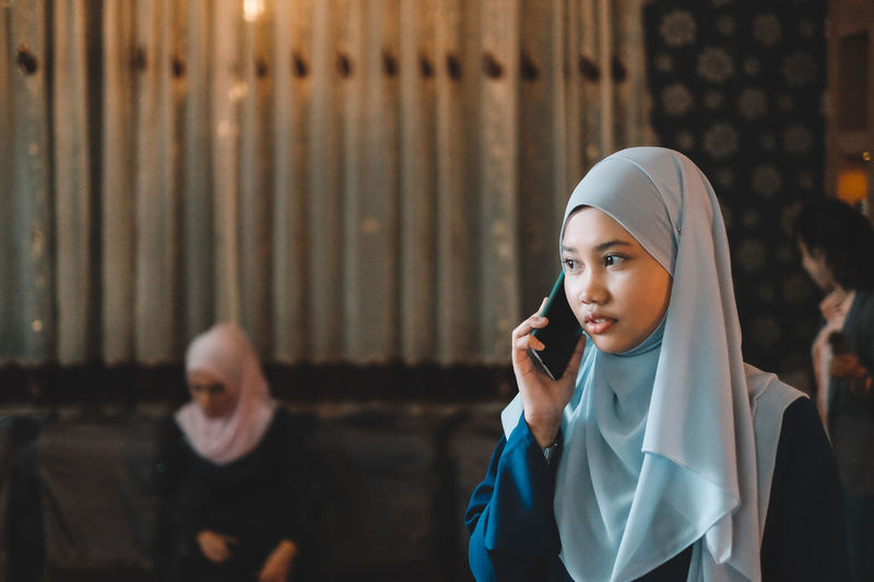 Young woman wearing hijab talking on mobile phone
