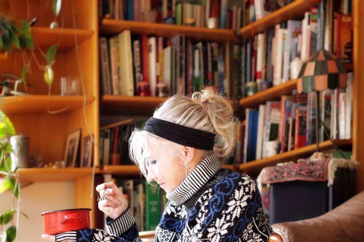 Senior woman sitting against book shelf at home