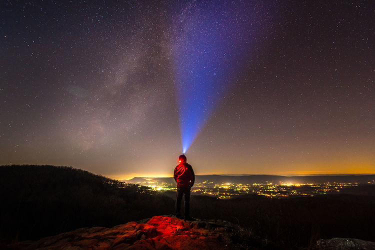 A person(s) or couple with flash light strapped to head winter clothes either standing or sitting on top of the rock at night looking at the stars and milky way with city light in the background long exposure. Be. Ready. Astronomy Beauty In Nature Constellation Discovery Exploration Flashlight Galaxy Illuminated Landscape Leisure Activity Milky Way Nature Night One Person Real People Scenics Sky Space Space Exploration Standing Star - Space Star Field Tranquil Scene Tranquility