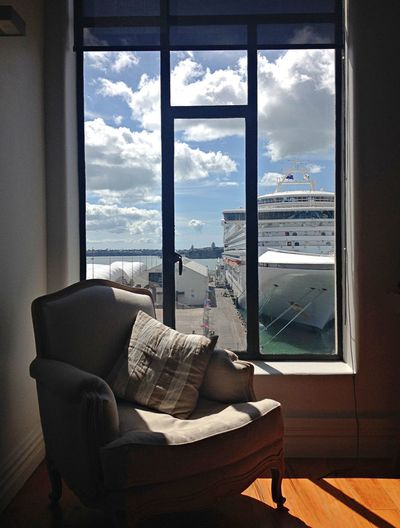 Empty armchair by window against cruise ship moored at harbor