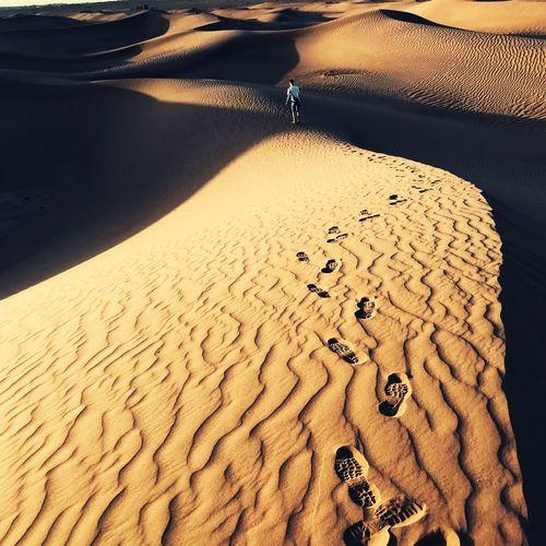 High angle view of man walking on sand dunes at desert