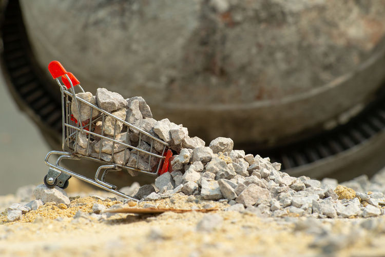 Selective focus on shopping trolley carries the crushed stones and pouring onto the pile at the construction site