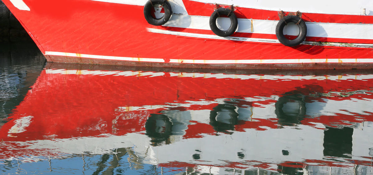 detail of a big red and white ship reflected on the sea water Fishing Boats Harbor Mirror Red Reflection On Water Transportation Travel Boat Commercial Dock Fishing Fishing Boat Mirror In The Water Mirror On Water Moor  Moored Mooring Ocean Ocena Portrait Reflect On Water Sailing Sea Shipping  Vessel Vessel In Port