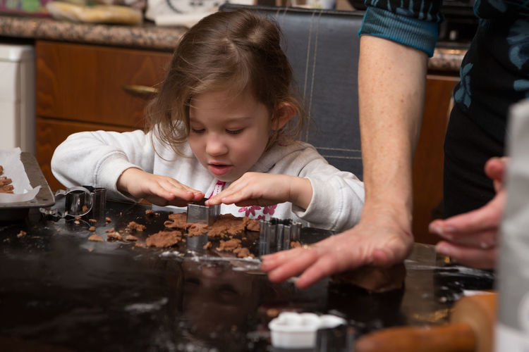 Girl Preparing Cookie With Mother On Kitchen Island At Home
