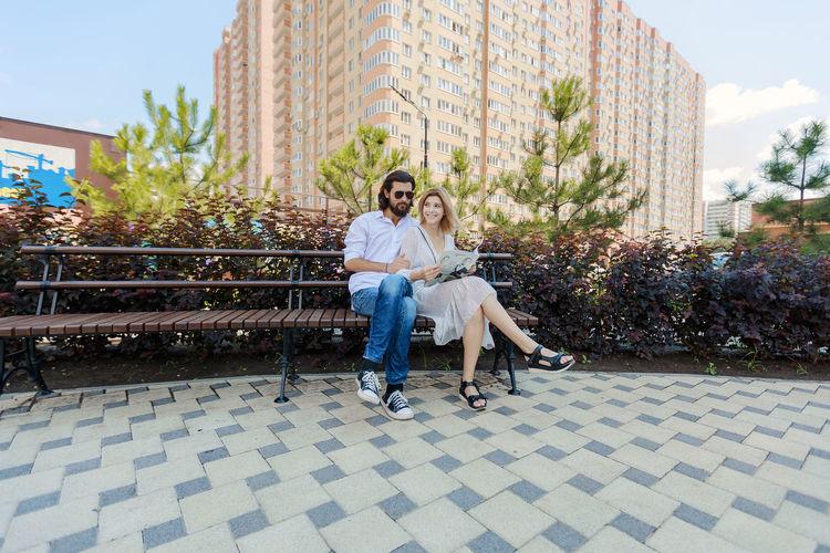 Full length smiling couple sitting on park bench