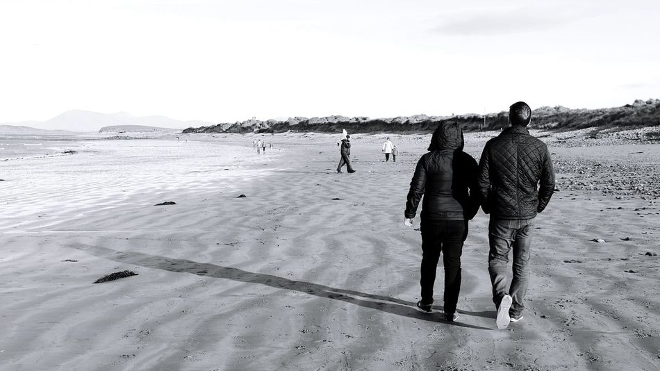 Beach Rear View Sea Real People Two People Outdoors Leisure Activity Sky Adults Only Walking Sand Togetherness Winter Full Length Day People Women Adult Men Water Travel Connemara Ireland Landscapes Ireland Coast Finding New Frontiers Traveling Home For The Holidays Black And White Friday