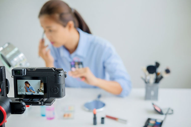 Activity Adult Camera - Photographic Equipment Concentration Connection Creativity Digital Camera Education Focus On Foreground Holding Indoors  Looking Occupation One Person Photographic Equipment Photography Themes Real People Table Technology Working