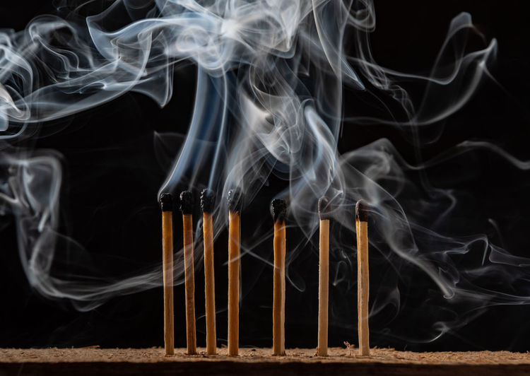 Close-up of emitting smoke against black background