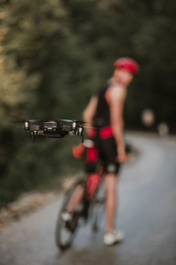 Close-up of drone flying while man with bicycle standing on road