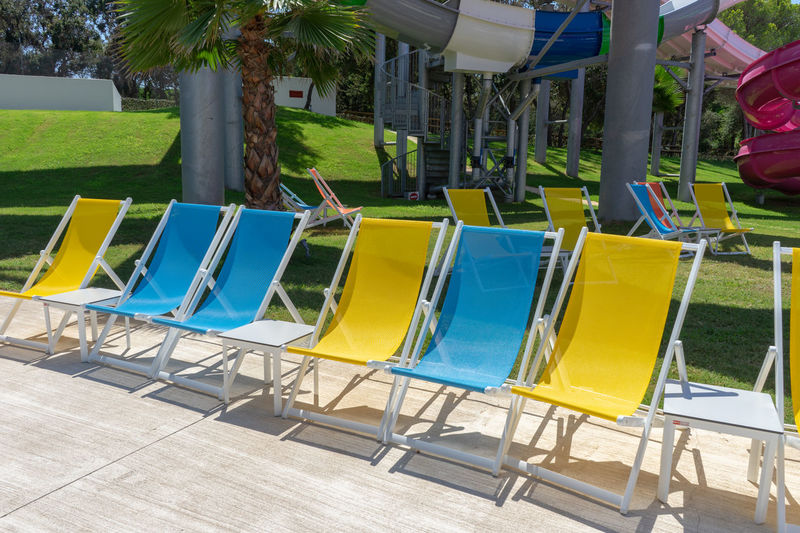 Colors Summer Vacation Absence Chair Colorful Day Empty Group Of Objects In A Row Land Lounge Chair Many Nature No People Outdoors Plant Pool Protection Seat Summer Sunlight Swimming Pool Tree Water Yellow