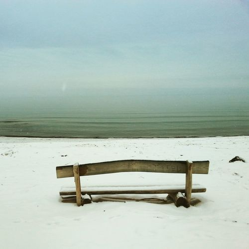 Empty Bench On Snow Against Calm Sea