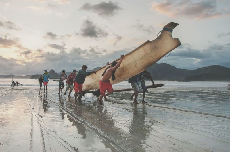 Fishermen Carrying Fishing Boat On Sea Shore Against Cloudy Sky