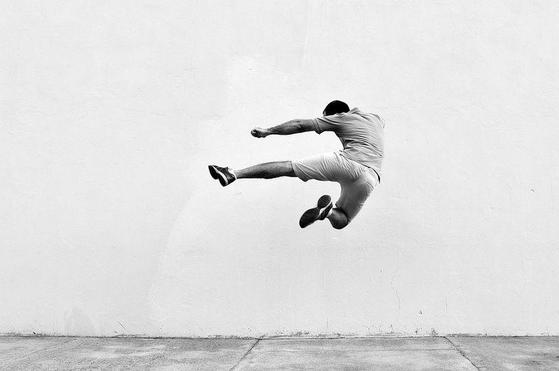 Man In Mid-Air Against Wall
