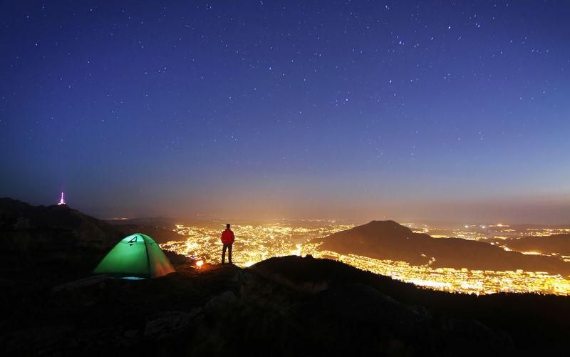 Man sitting against illuminated mountain against sky at night