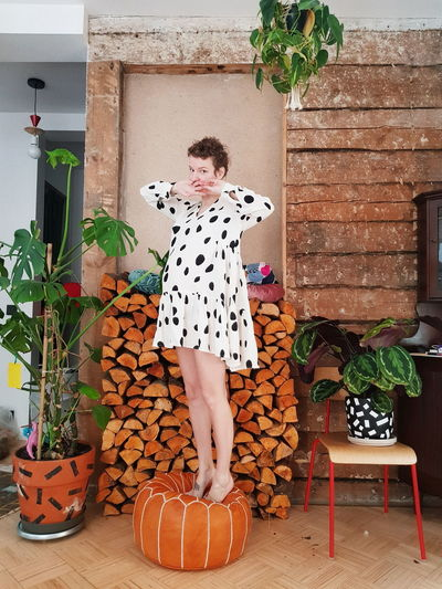 Woman standing by potted plant