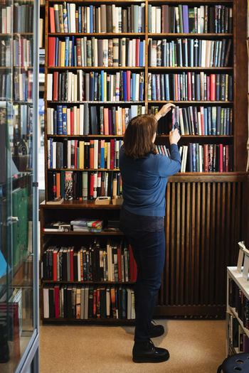 Rear view of woman standing in library