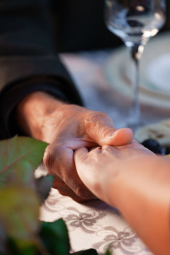 Old man and woman hold hands at a romantic dinner at a restaurant