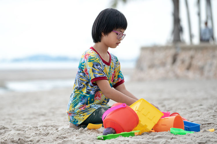 Portrait Asian girl with eyeglasses builds the sand castle on the beach by colourful models Beach Land Child Childhood One Person Water Lifestyles Real People Leisure Activity Sand Toy Casual Clothing Focus On Foreground Boys Day Sea Nature Sand Pail And Shovel Innocence Outdoors Model Sand Dune Castle Playing Fun