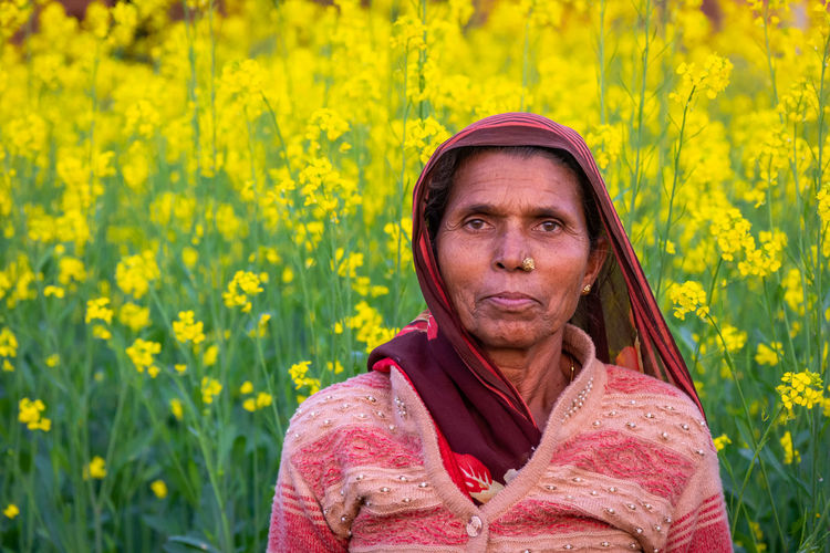 Portrait of senior woman with yellow flower in field