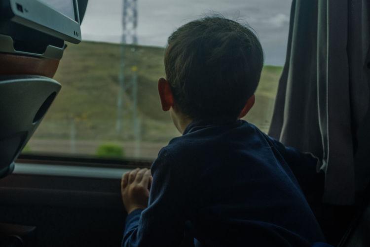 Boy looking through train window