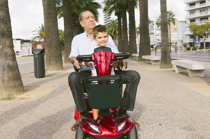 Grangfather and child on a motorized chair Grandfather Bonding Boys Child Childhood Day Electricity  Emotion Family Family With One Child Father Males  Mature Men Men Motorized Offspring Outdoors Parent Positive Emotion Son Togetherness Transportation