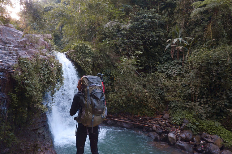 Gazing at the waterfall with a big backpack
