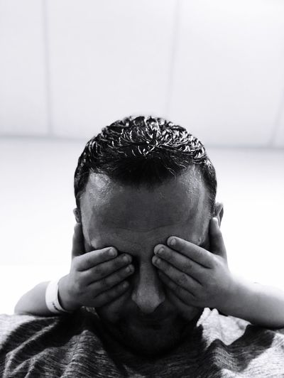 Cropped hands of child closing man eyes