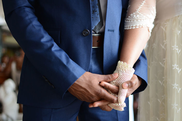 Midsection Of Newly Wed Couple Holding Hands During Wedding