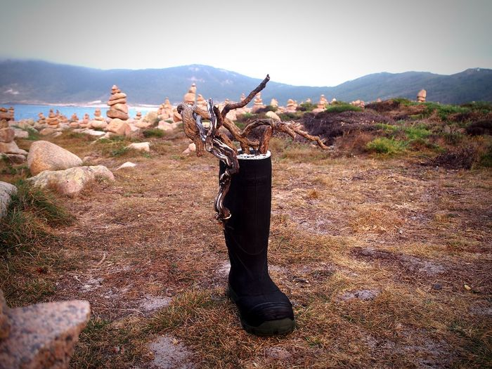 Black boot on land against mountains