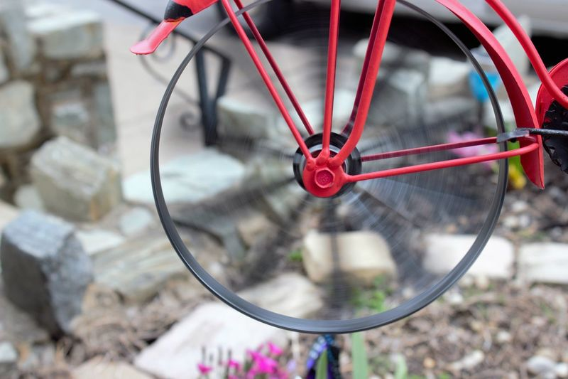 Wheel spinning on bike garden decoration Bike Bike Wheel Garden Decor Garden Photography Object Photography Objects Outdoor Photography Red Spinning Bike Wheel