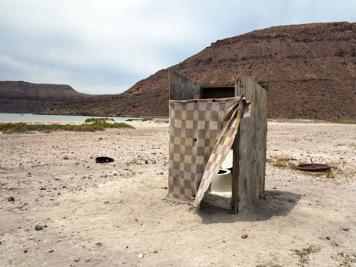 Outhouse by mountain at desert against sky