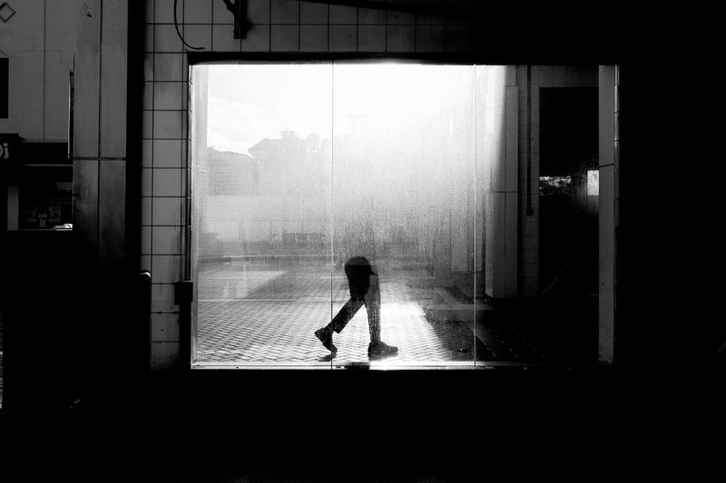Person seen through wet window during rainy season