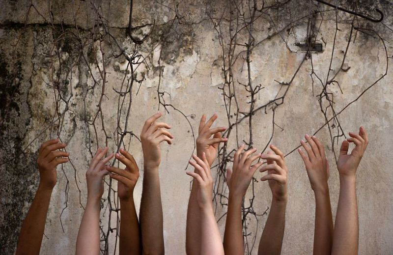 Cropped hands of women against wall