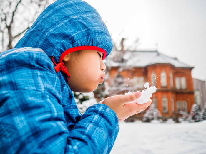 Side view of boy playing with snow while sitting outdoors