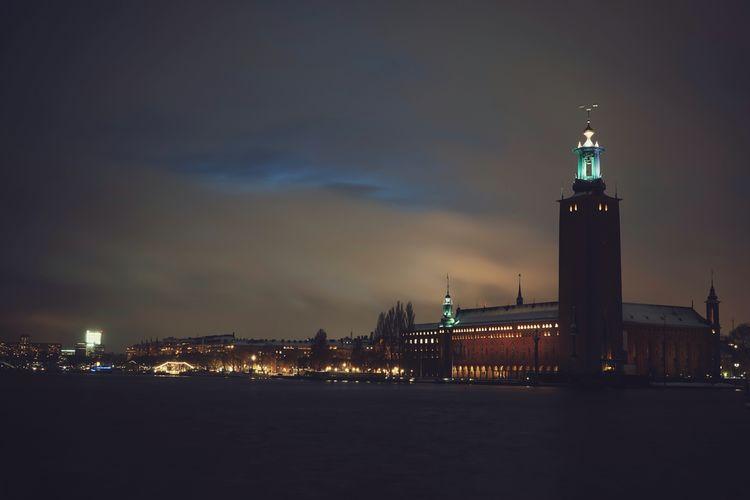 Illuminated buildings against cloudy sky at dusk