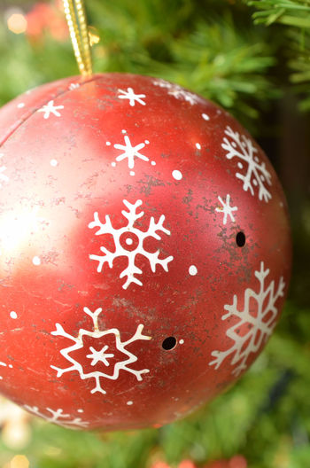 vintage metal ball ornament red with white snowflake pattern hanging on green Christmas tree Celebration Christmas Christmas Decoration Christmas Decorations Christmas Ornament Christmas Tree Close-up Focus On Foreground Hanging No People Red Tradition Vintage Christmas Decorations