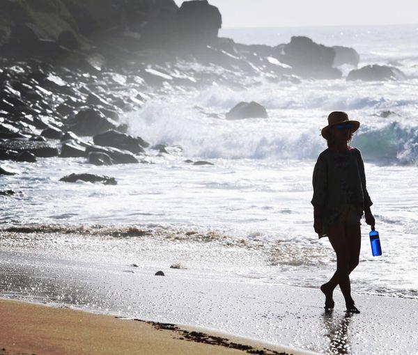 Full length of woman walking on shore at beach