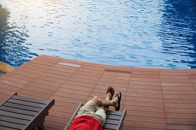 High angle view of man relaxing on chair by swimming pool