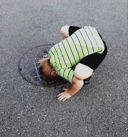High Angle View Of Boy Crouching On Manhole At Street