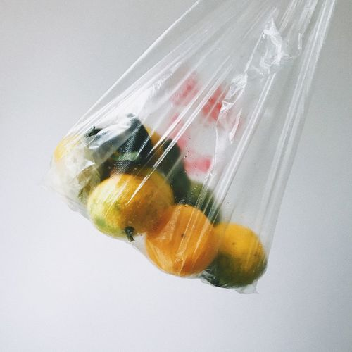 Close-up of fruits in plastic bag over white background