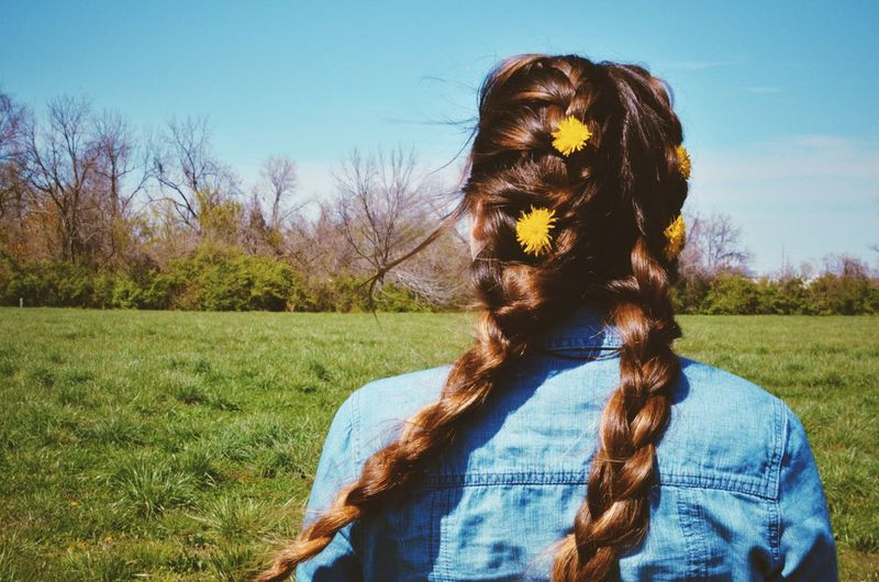 Rear view of woman wearing flowers on hair at grassy field